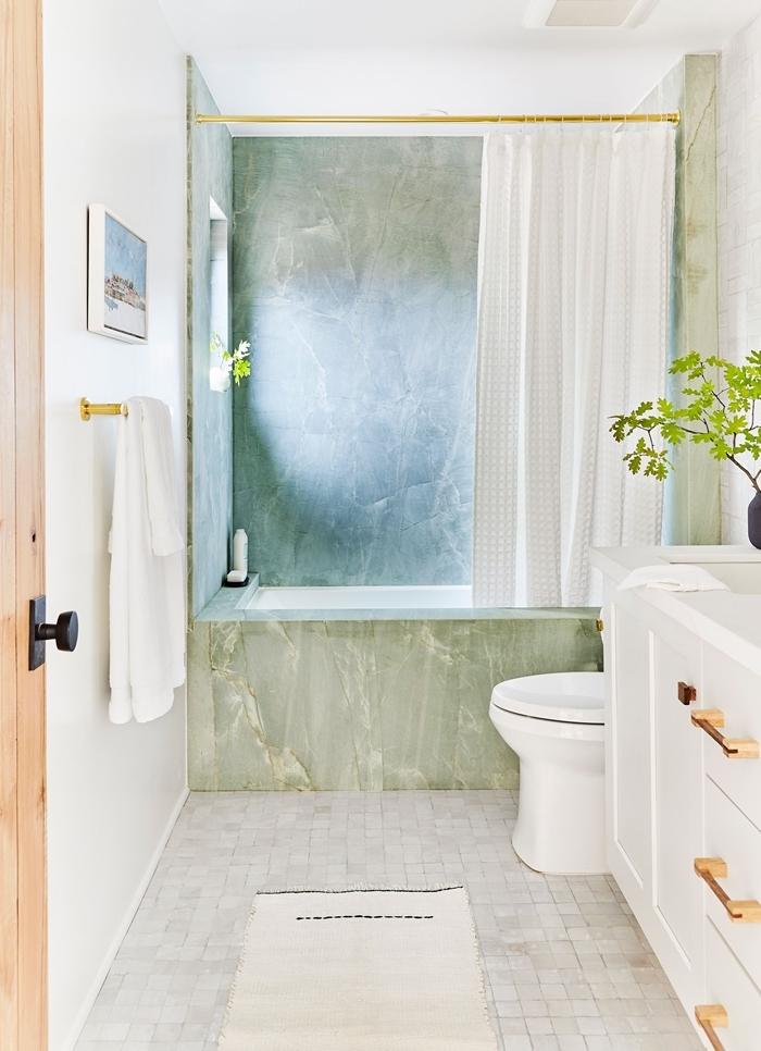 tapis de bain blanc carrelage gris clair rideaux baignoire modele salle de bain séche linge plante verte