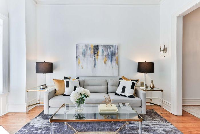 tapis gris anthracite plafond haut sol en parquet clair canape gris avec des coussins colorés
