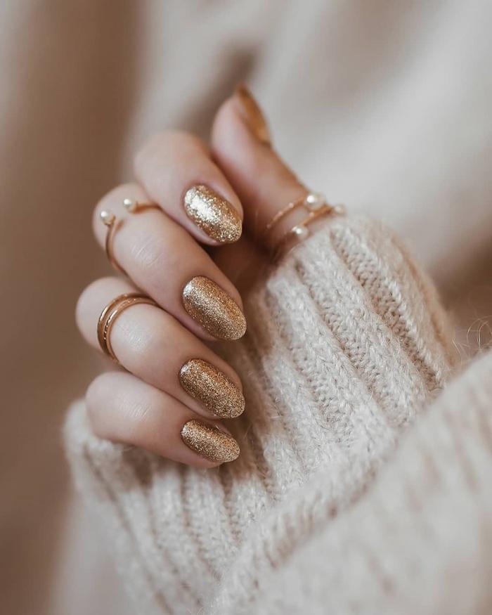 tendance nail art pour noel manucure ongles amandes vernis couleur or effet pailleté bijoux femme or bagues perles