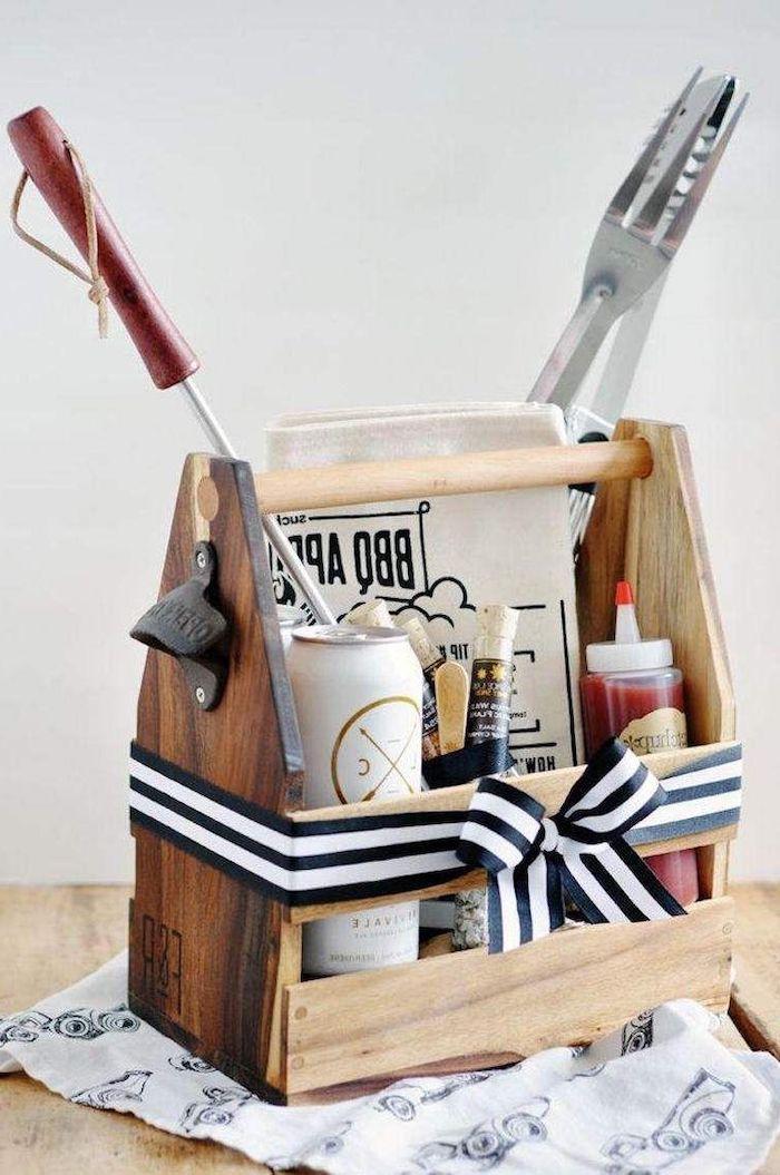 un ensemble pour faire de la barbeque avec des couverts de la biere er des sauces dans un panier en bois idée de cadeau pour anniversaire
