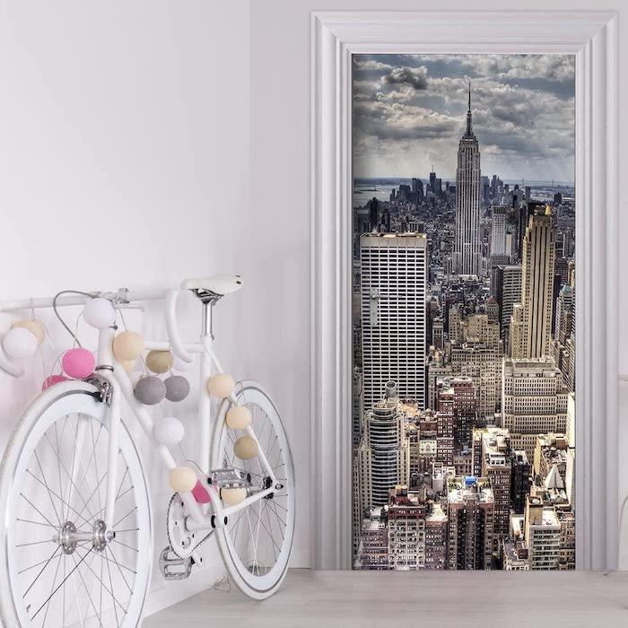 un sticker mural sur la porte a cote d un bicyclette blanche