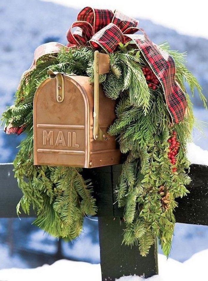 une boite a lettres decoree pour noel avec des branches de sapin et un ruban carre