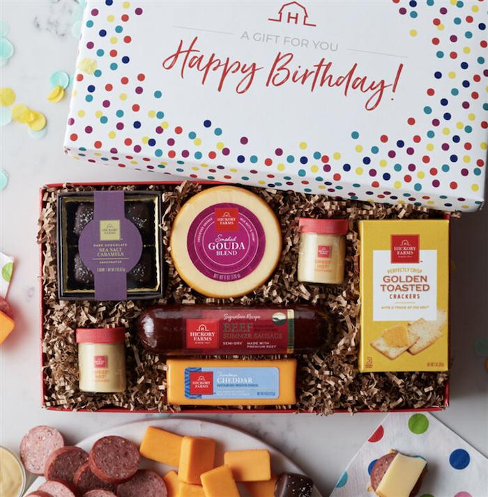 une boite avec des petits cadeaux delicieux de frommage de saucisson et des chocoats idee d envoyer a un ami pour son anniversaire