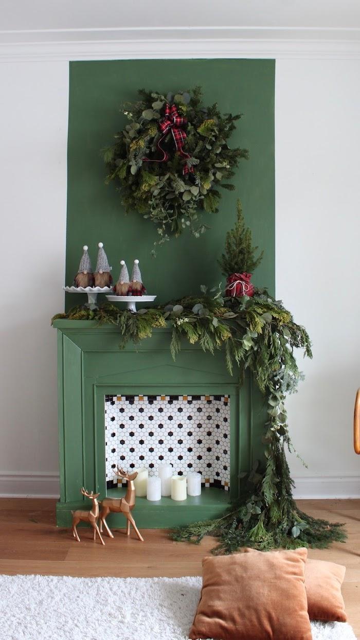 une fausse cheminée verte décoree aves des bougies et beaucoup de la verdure pendante