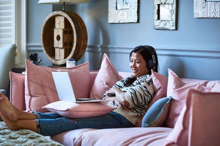 une femme adulte parle sur l ordinateur dans son canape rose que faire le jour de son anniversaire