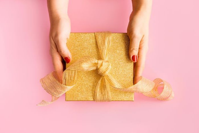 une femme qui tient un cadeau avec un papier d oree quoi d offrir pour une anniversaire en confinement