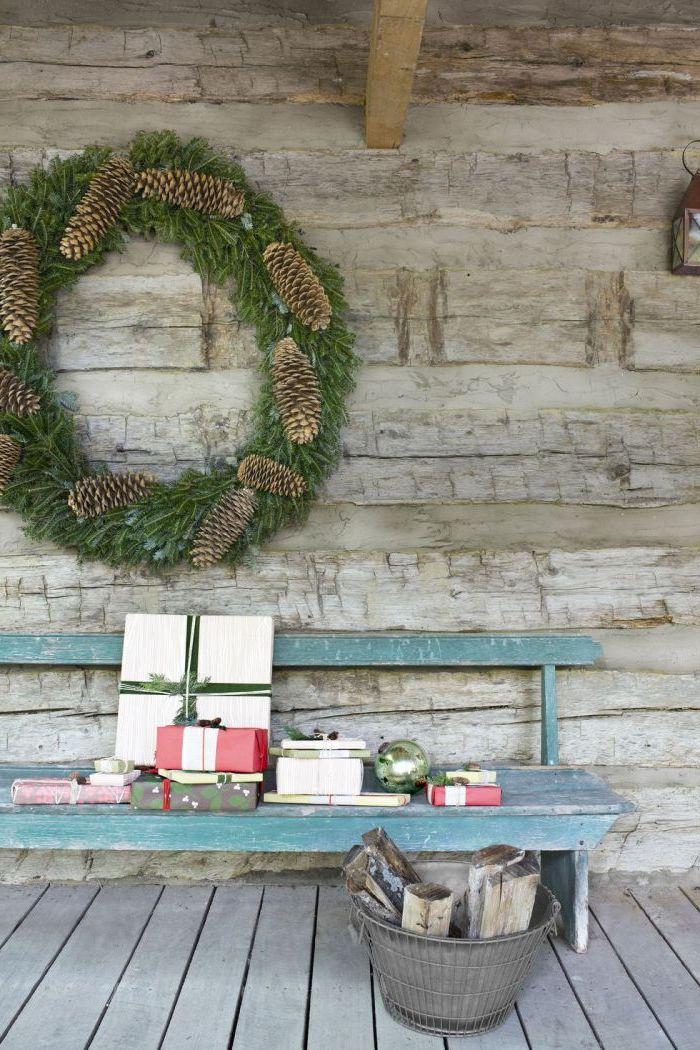 une grande couroonne de branches de spin avec des cones de pin faite en main au dessus d une banquette bleue en bois style rustique