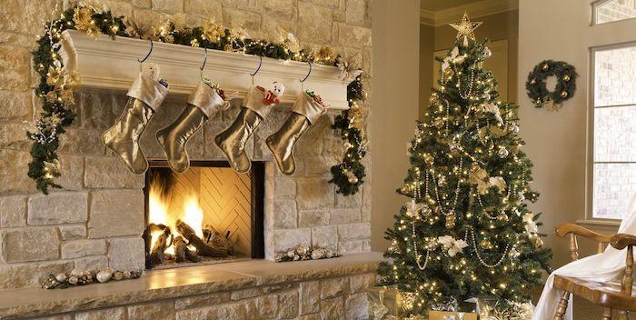 une idée de décoration de noel thématique en or avec des chaussettes suspendus au dessus de la cheminee