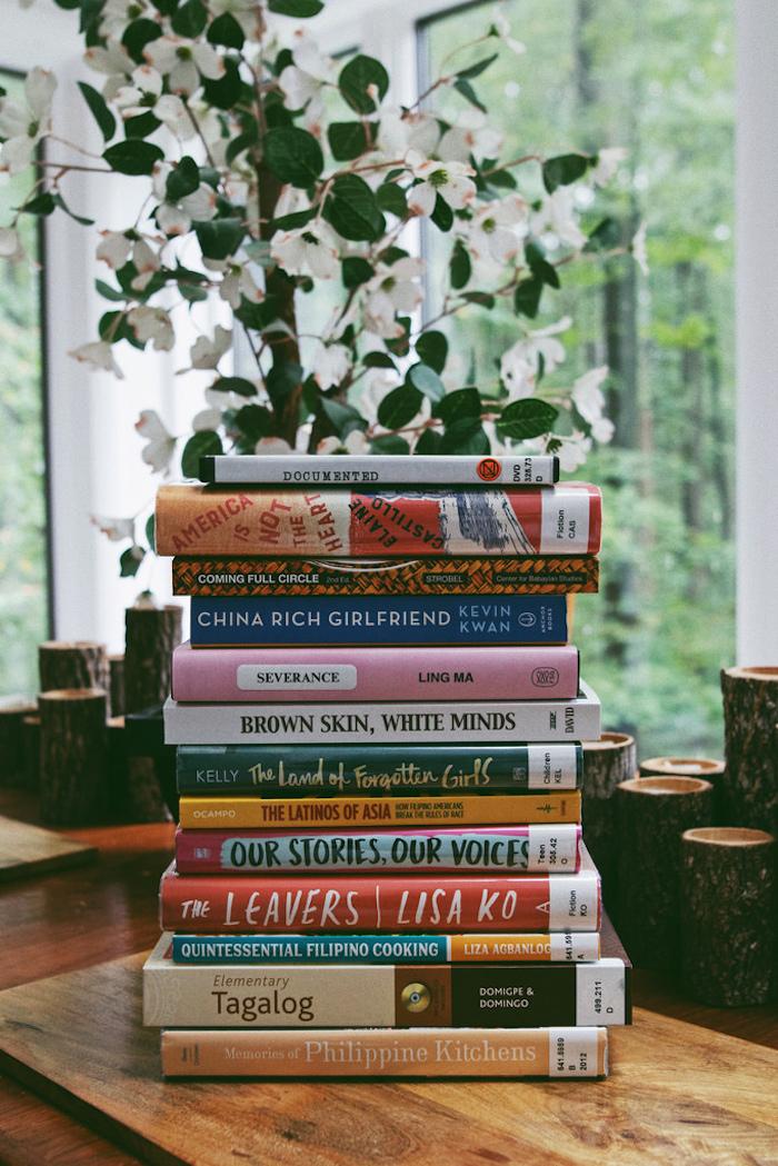 une idee de cadeau d anniversaire en confinement une pile de livres ranges un fenetre au fond derriere une plante verte