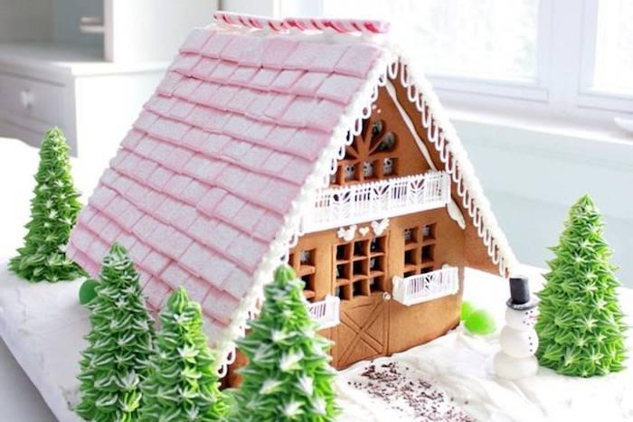 une maison en pain d épices avec un grand toit rose et des sapins comestibles dessert de noel facile