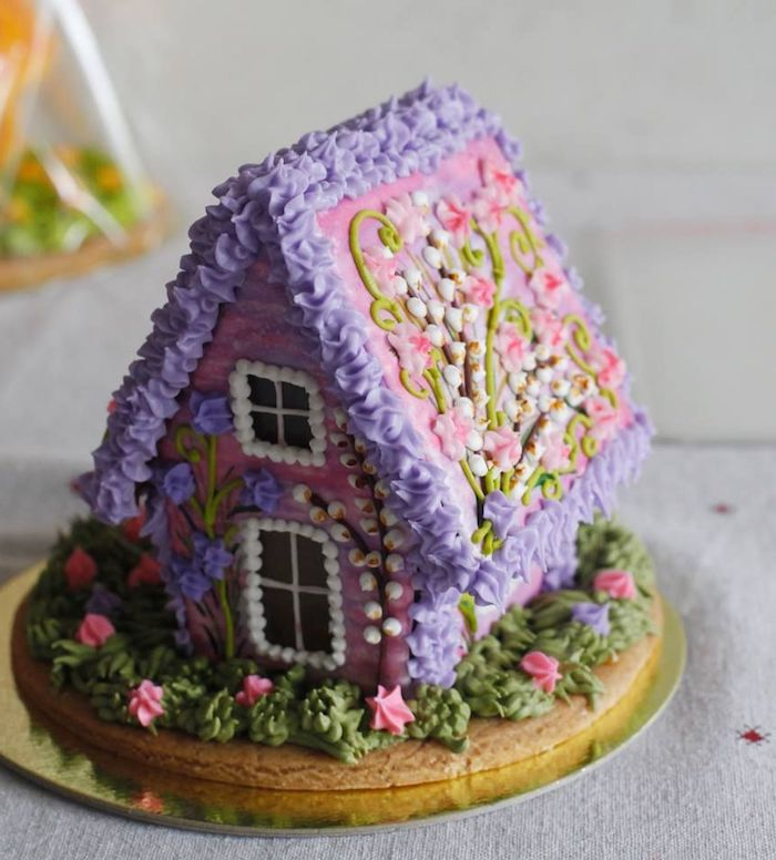 une maison en pain d épices decorée de fleurs en creme violet et rose idee de dessert de noel