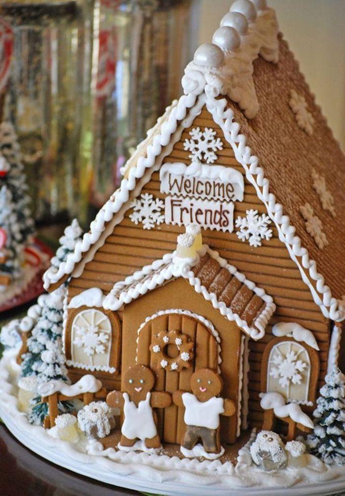 une maison en pain d épices heut de gamme décorée avec des petits bonhommes de gingembre devant la porte sapins decoratifs