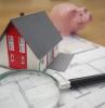 une modele de maison avec une loupe et plan de rennovation