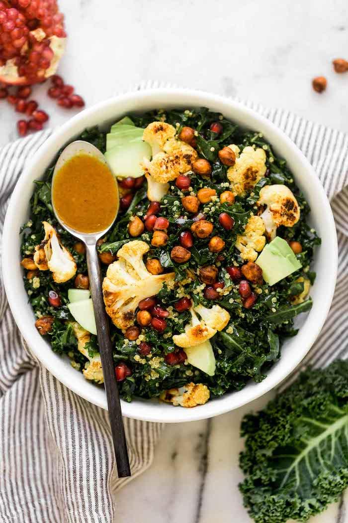 une salade de chou frise avec un dressing graines de pomegranate et des pois de chiche