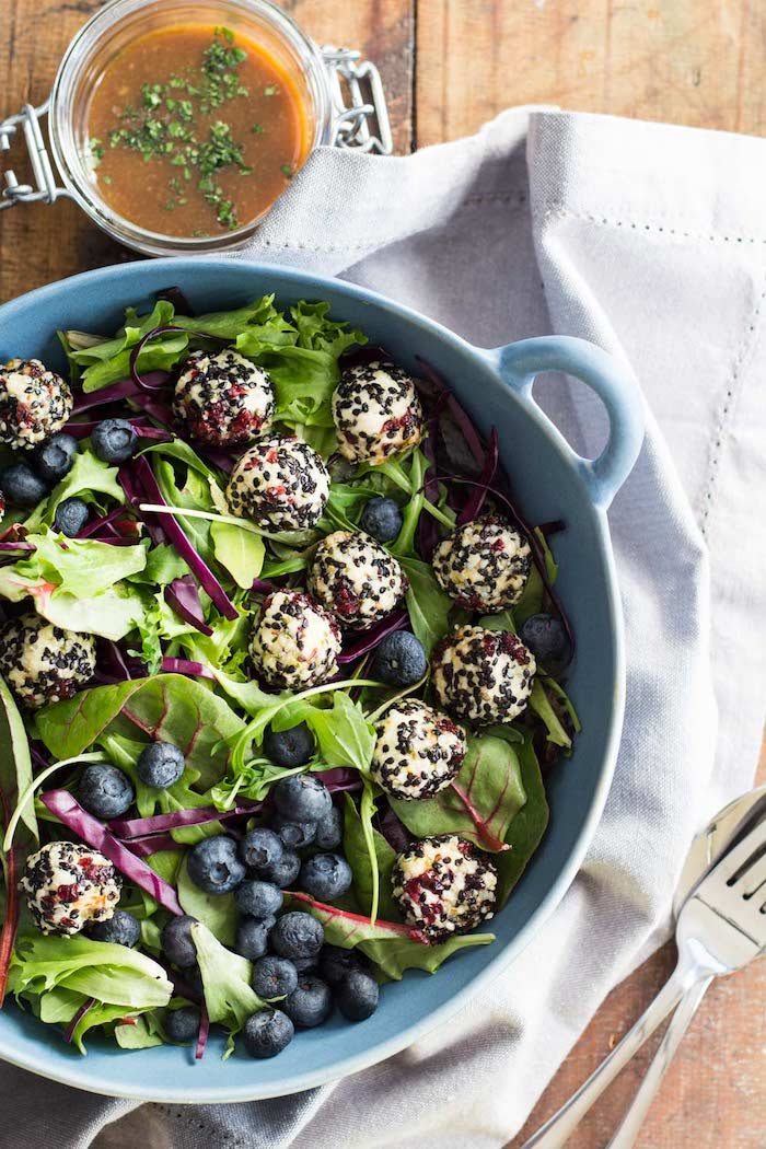une salade de fruits hiver des myrtilles et des epinards avec frommage chevre servie avec une soupe creme