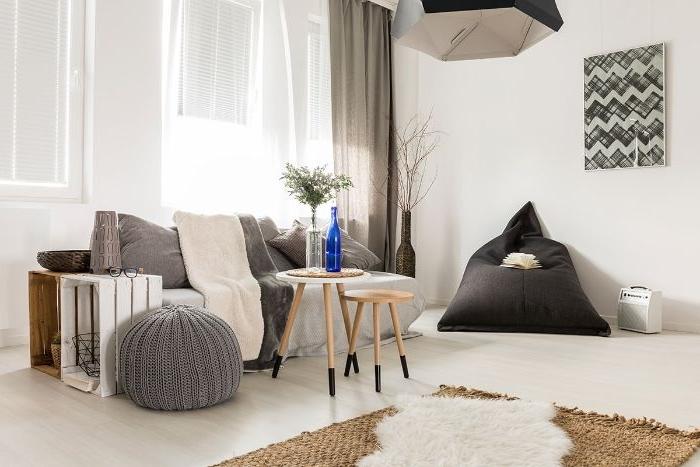 ambiance cocooning deco salon gris et blanc scandinave avec pouf gris plaids cocooning tapis peau animal assise grise par sol