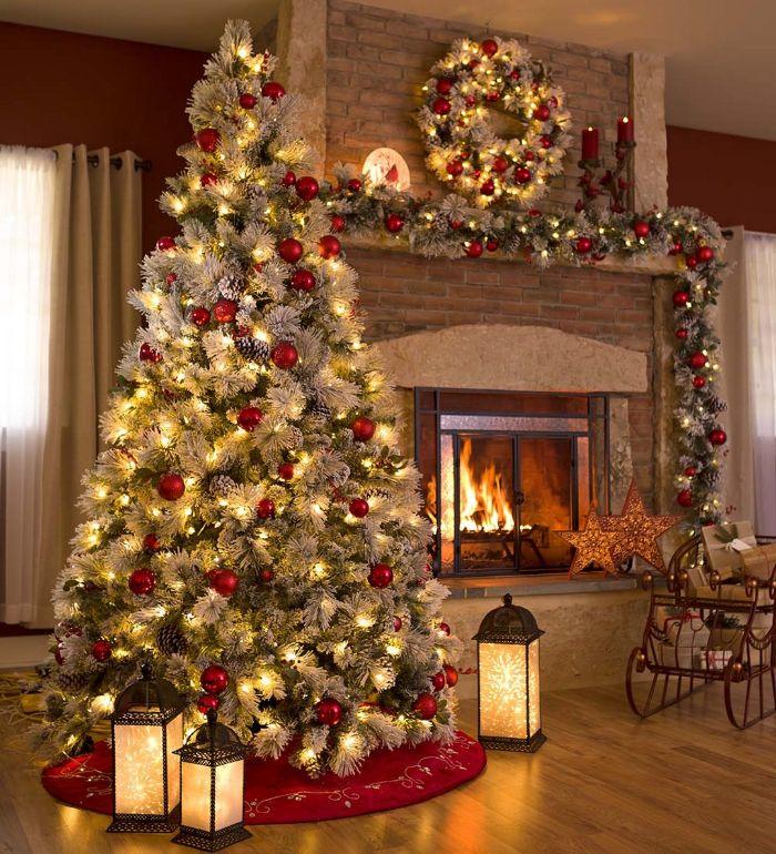 ambiance cosy sapin de noel décoré en vert et branches blanches et des boules de noel rouges et lumieres près d une cheminée de noel décorée