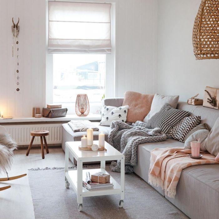 ambuance depaysante coin cocooning salon gris clair et blanc avec coussins csy et table basse blanche à roulettes murs blancs