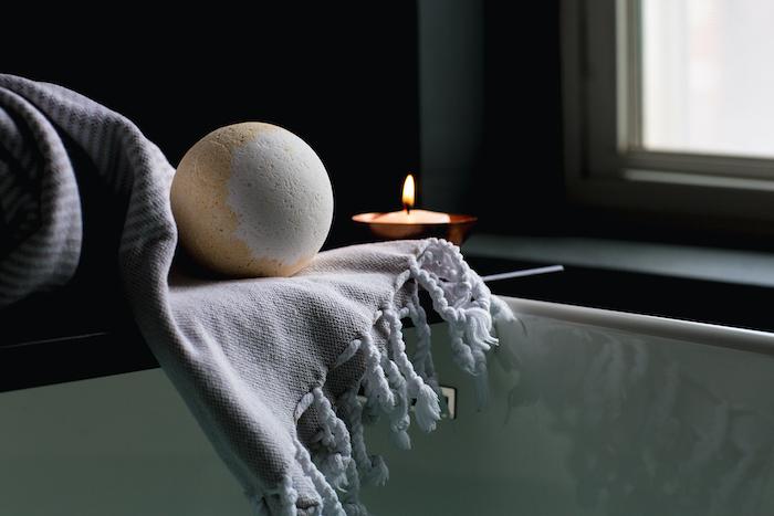 bombe de bain maison en couleur neutre sur une serviette et pres dun bougie