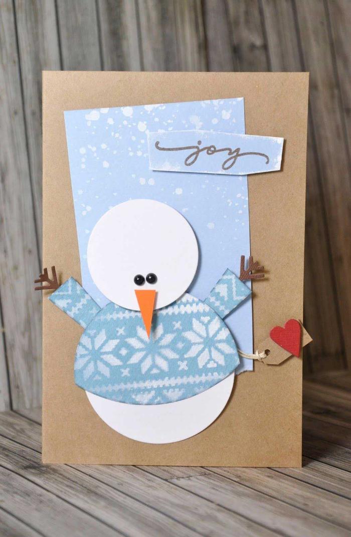 bonhomme de neige de papier blanc avec pull motif flocon de neige sur fond bleu idée carte de noel maternelle papier kraft