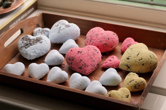 boule de bain bio dans une forme de coeur en differentes dimensions poses dans un plateau en bois