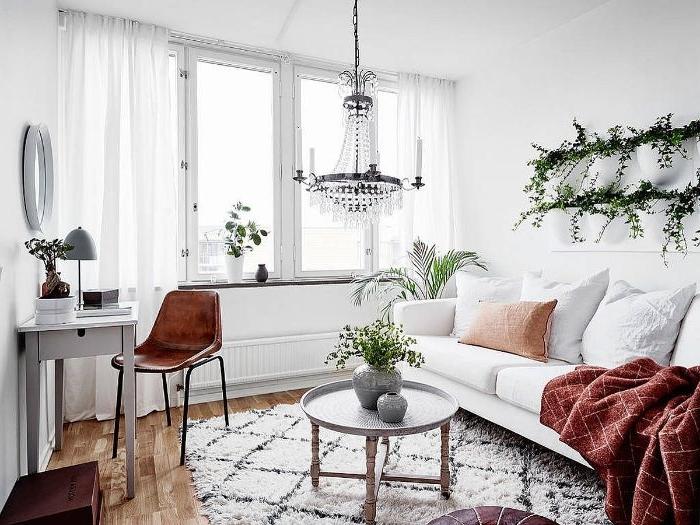 branches vertes decoratives dans salon cosy blanc aux accents cuire rideaux blanches parquet bois clair suspension lustre original