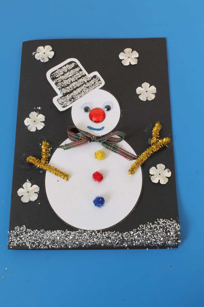 bricolage noel maternelle facile carte dans papier noir avec bonhomme de neige papier blanc pompons colorés des yeux mobiles