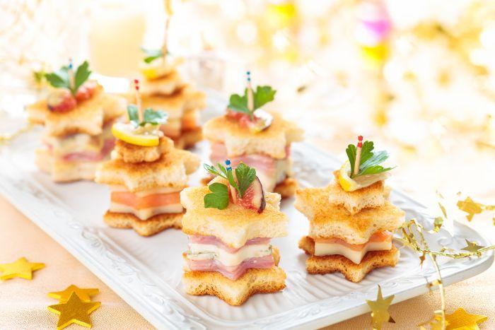 brochette apero de noel idée de petit sandwich étoile de pain grillé jambon et fromage dans plateau
