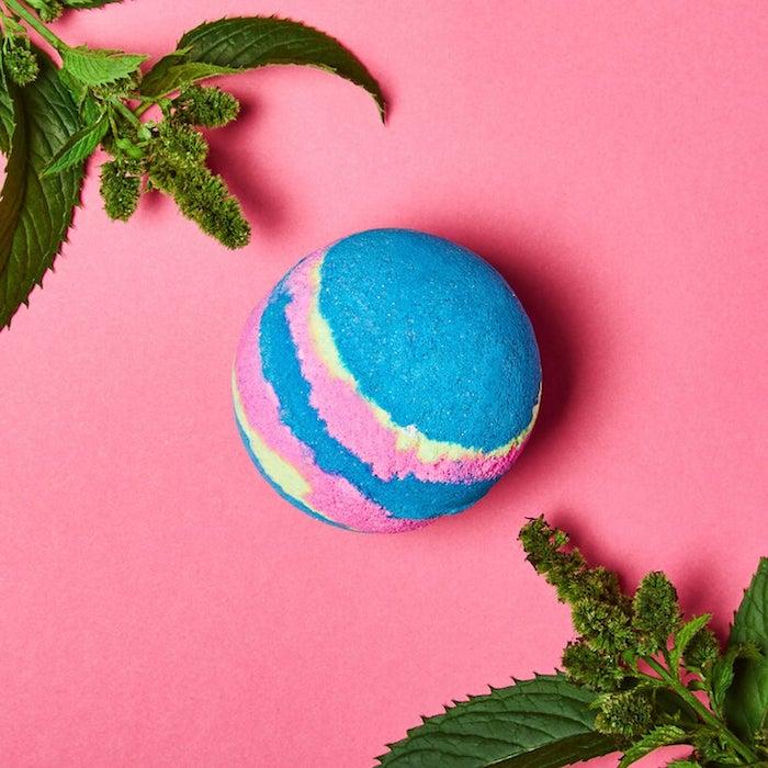 cadeau femme anniversaire avec une boule de bain multicolore sur une surface rose entre deux branches vertes