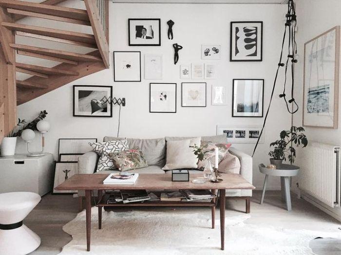 cadres deco noir et blanc sur mur blanc table basse bois vintage canapé surchargé de coussins décoratifs escalier bois