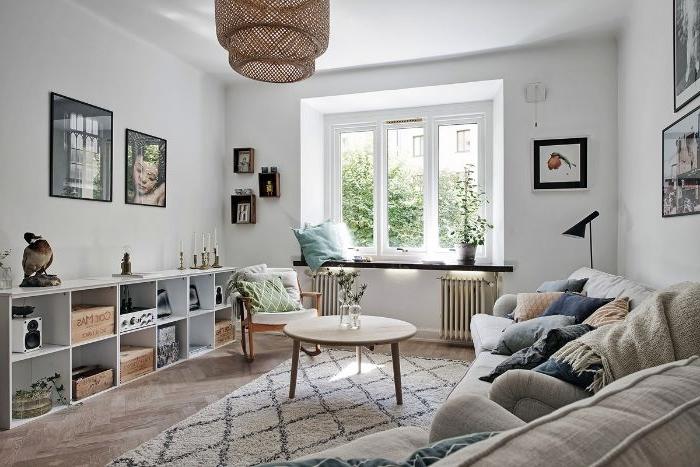 canapé cocooning gris décoré de multitude de coussins table basse ronde rangement ikea bas murs blancs suspension tendance