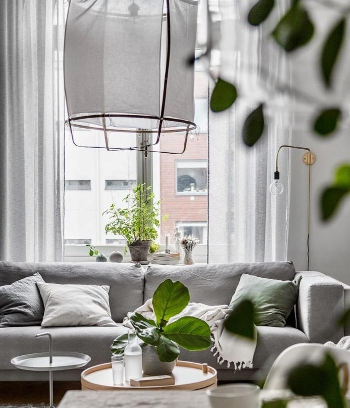 canapé gris clair table basse bois rideaux blanches grandes fenetres d un salon cocooning chic à la scandinave
