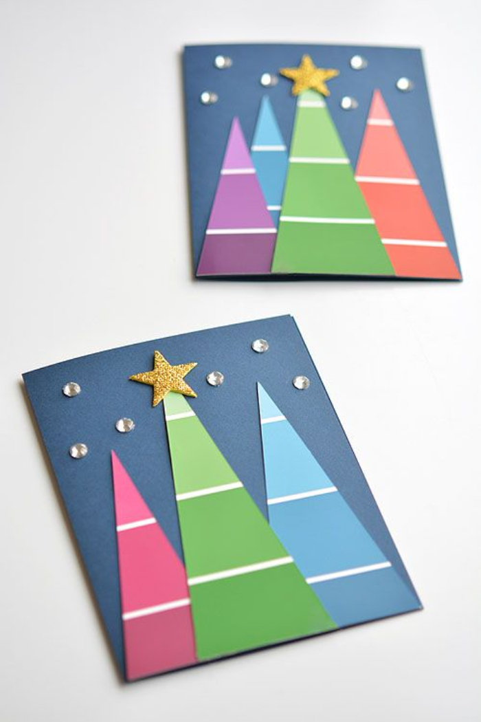 carte de noel a fabriquer avec des sapins de papier coloré avec décoration d étoile et strass sur papier bleu
