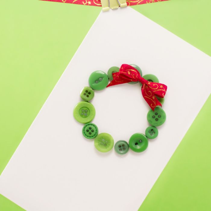 carte de noel fait main idée couronne de noel en boutons verts décorés de ruban rouge sur bout de papier blanc