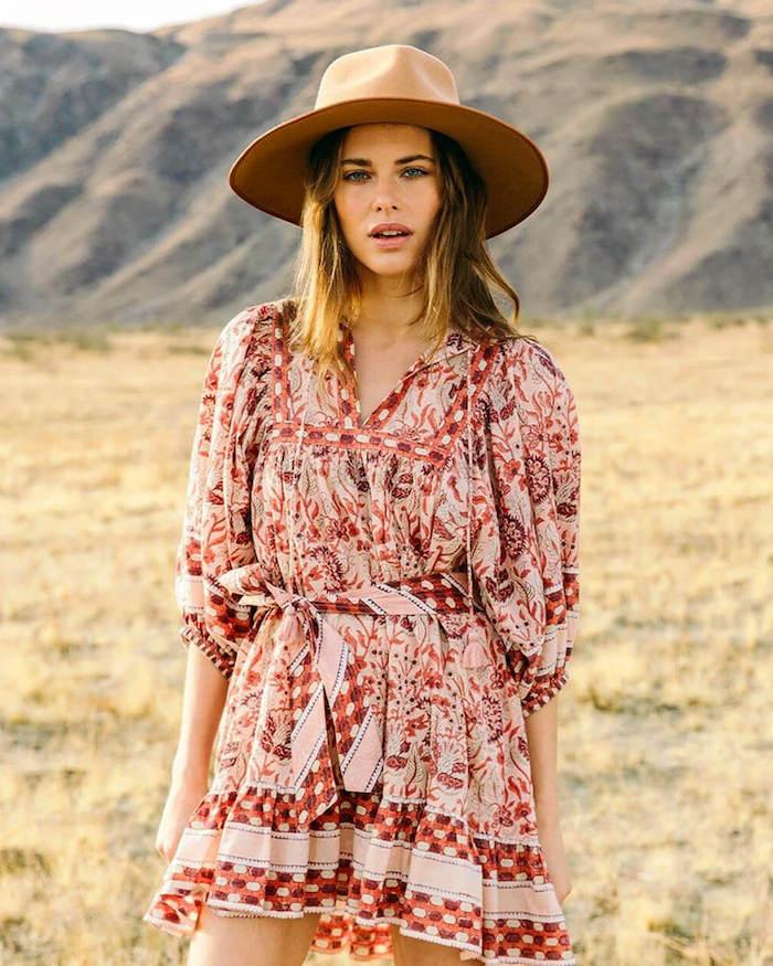 casual chic femme avec une robe courte decontractée et chappeau aux larges bordes une femme devant la montagne