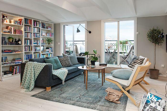 chaises scandinaves grande bibliotheque desugn canapé scandinave plaid cocooning tapis gris effet usé murs gris perle