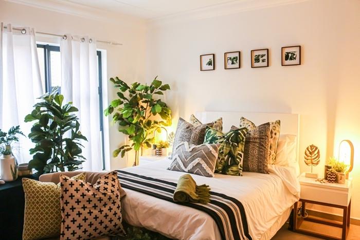 chambre parentale cosy plantes vertes chambre adultes mur cadres photos blanc et noir coussins décoratifs