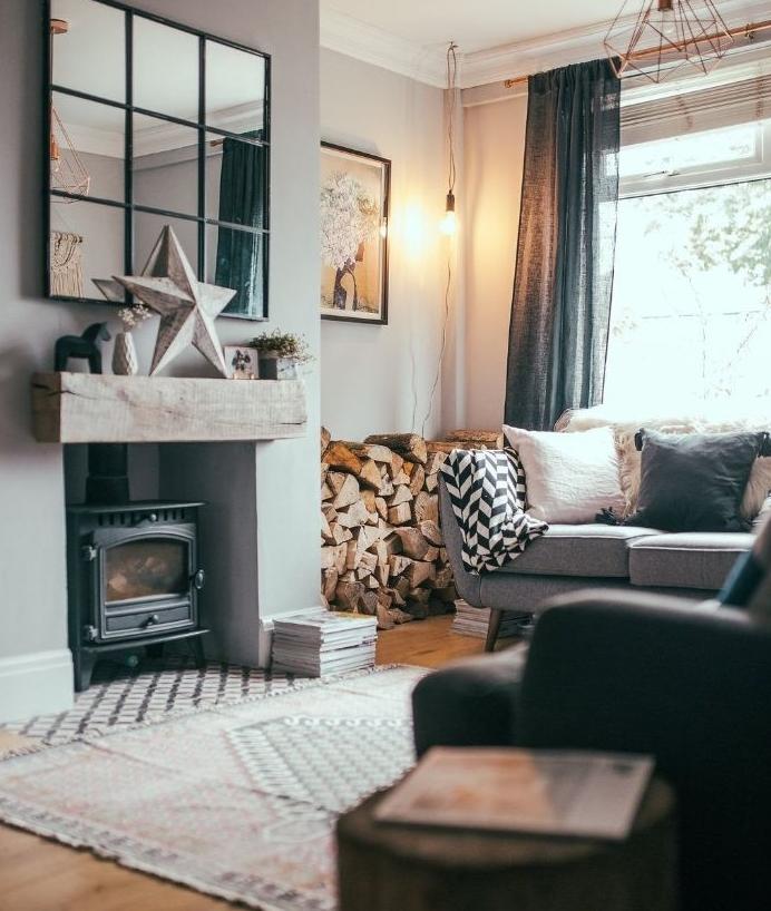 cheminée noire tapis vintage bois stocké dans un angle canapé gris foncé parquet bois clair miroir à carreaux
