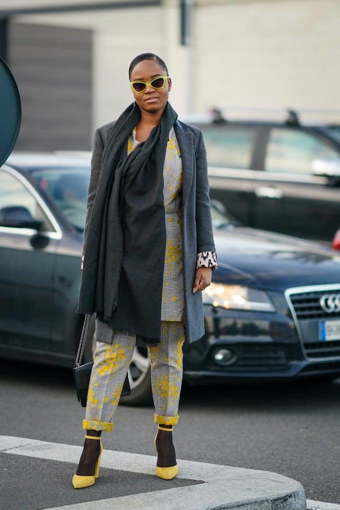 code couleur pantone une femme en tailleur gris et des escarpins jaunes avec des lunettes des soleil devant une voiture