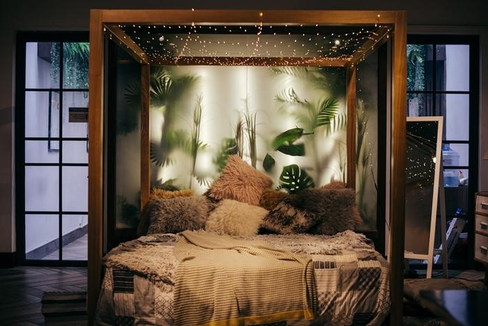 cosy déco chambre cocooning cadre de lit bois guirlande lumineuse mur végétal verre coussin fausse fourrure