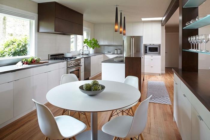cuisine équipée moderne table à manger ronde blanche chaises plan de travail gris armoires marron