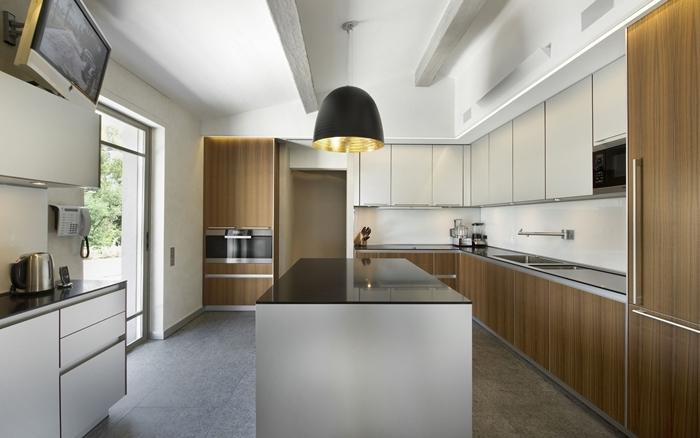 cuisine avec ilot central déco bois et blanc lampe suspendue noire plan de travail noir plafond poutre