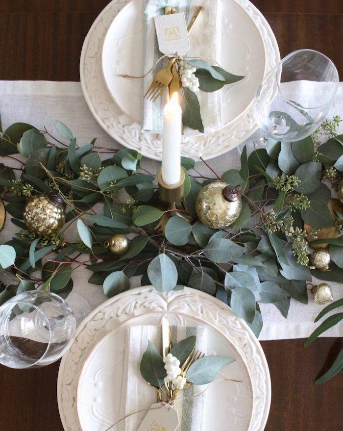décoration de table de noël avec des éléments naturels et des boules une bougie allumée entre deux assiettes en porcelaine