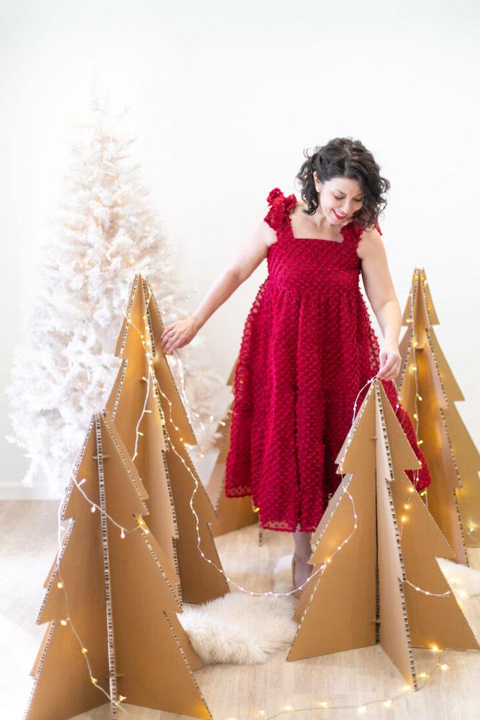 deco de noel fait main une femme en)robe rouge a cote des trois sapin)en carton avec des lumieres