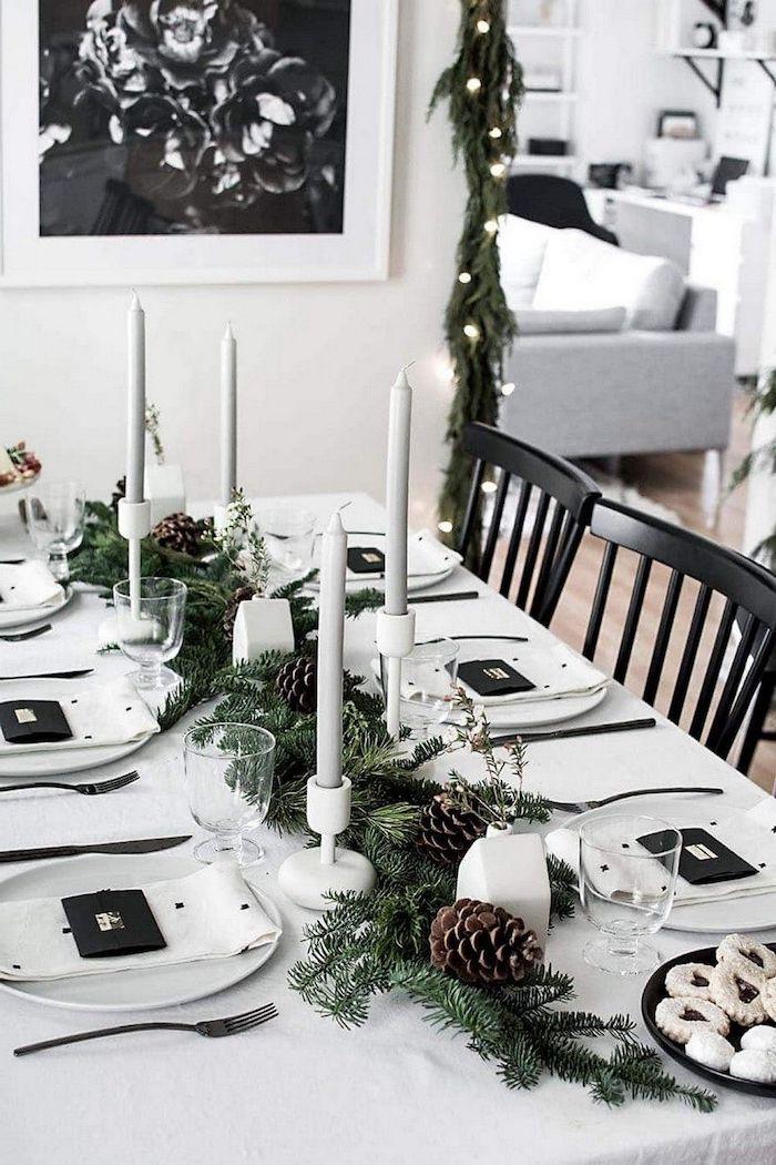 deco de table noel avec des branches de sapin et des cones de pin une thématique en noir et blanc avec des bougies et des assiettes porcelaines