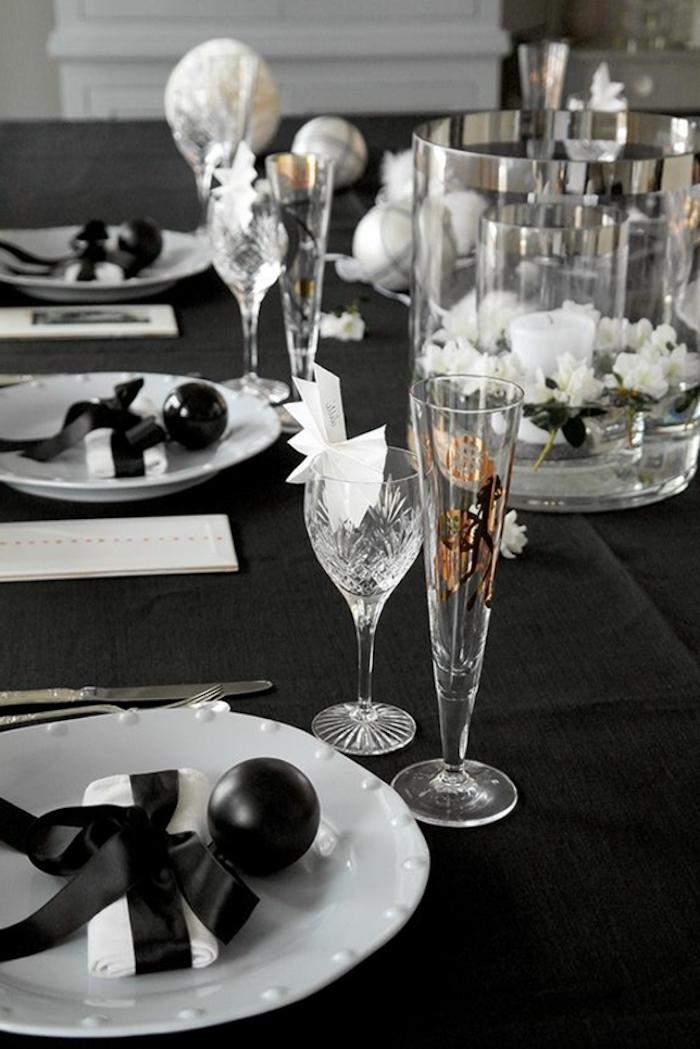deco jou de l an en noir avec des assiettes blanches et verres cristalles un bouquet au milieu de la table