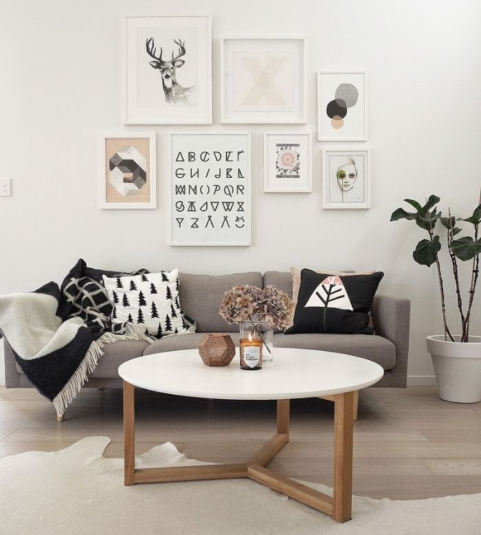 deco murale originale en tableaux d art graphique abstrait dans salon chaleureux avec table basse blanc bois canapé gris décoré de coussins parquet bois clair