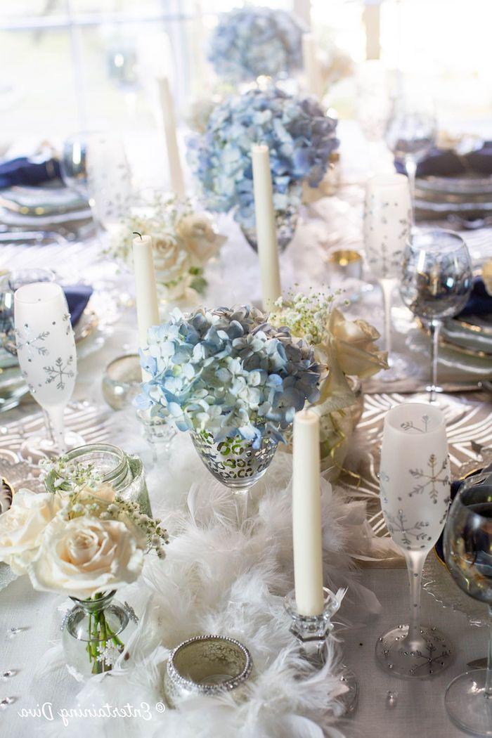 deco nouvelle an avec des roses et des fleurs bleus dans des verres de champagne une decoration de table avec des plumet