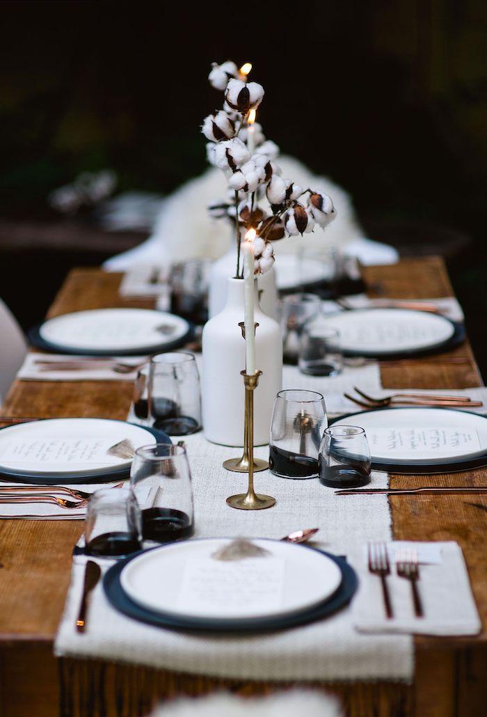 deco nouvelle an minimalistique avec des bougies et des branches de cotton sur une table rustique des couverts en cuivre