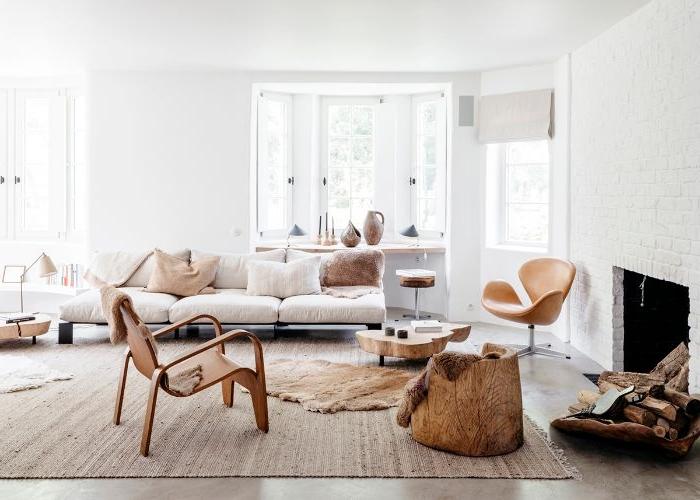 deco salon scandinave style minimaliste avec canapé bas avec coussins gris clair chauses tabouret bois cheminée blanche moderne murs blancs
